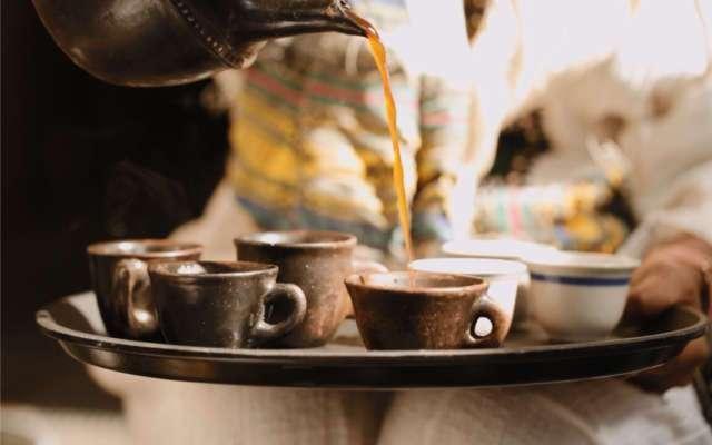 Der fertig gekochte Mokka wird mit Hilfe der Jabana auf die vielen kleinen Mokkatassen verteilt.