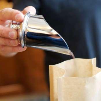 Frisch geröstete Kaffeebohnen, verpackt in braunen Kaffeetüten