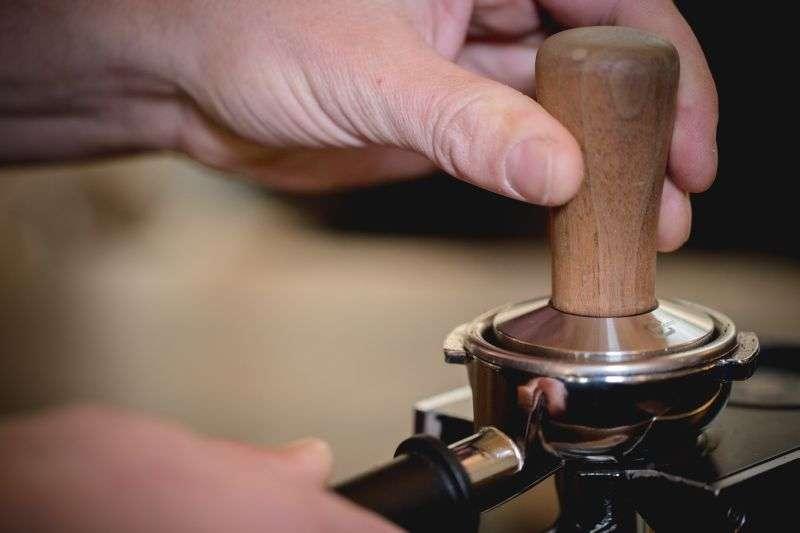 Drehe den Tamper auf dem festgedrückten Kaffeepulver, um die Oberfläche zu glätten.