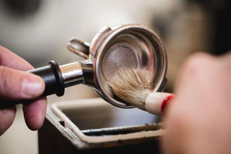 Reinige den Siebträger von alten Kaffeeresten mit einem Pinsel.