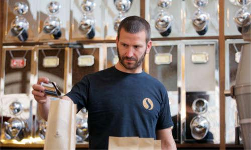 Röstmeister Andreas Raab beim Einfüllen der Kaffeebohnen in Pakete